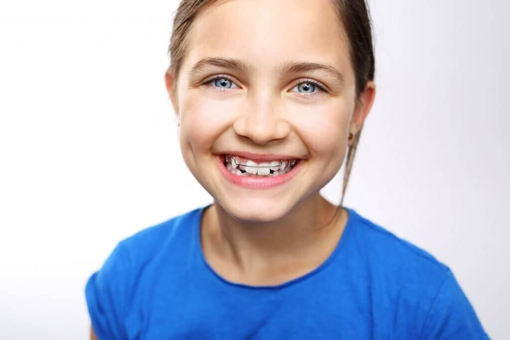Stop bedwetting with orthodontics, girl smiling with orthodontic appliance