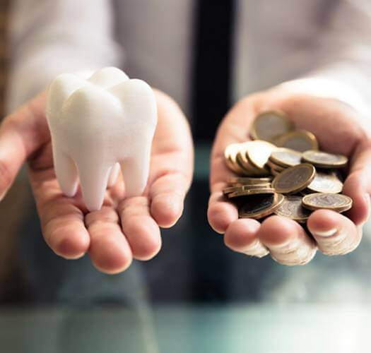 Cost of avoiding the dentist, hand holding tooth and hand holding coins