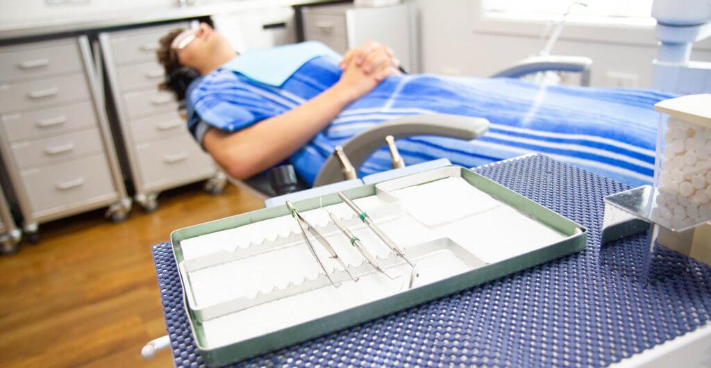 Sleep dentistry, patient sedated in dentist chair
