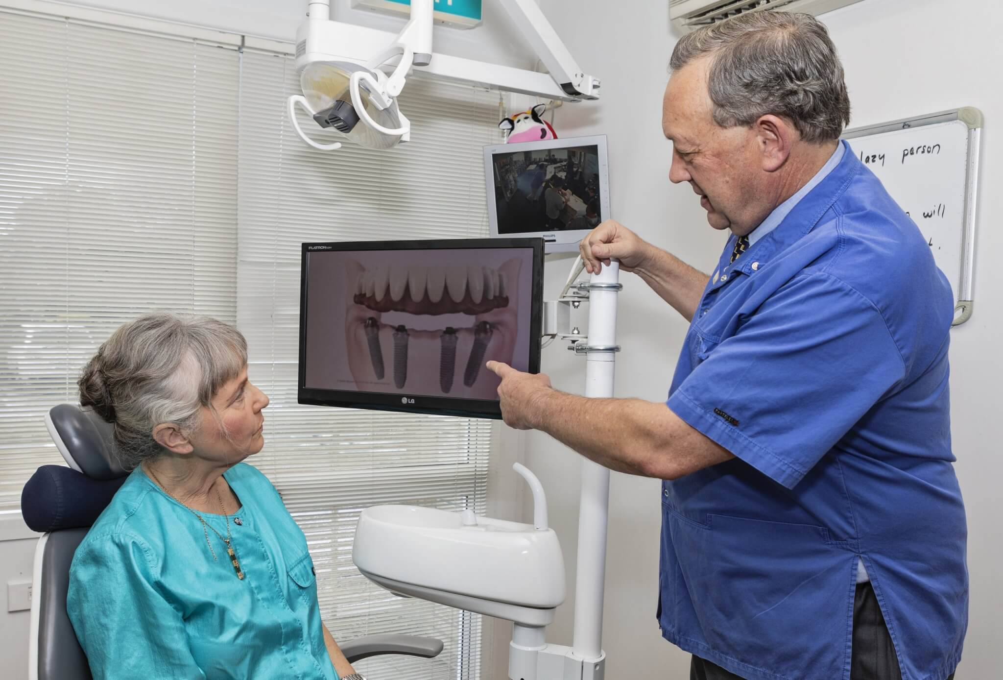 Dental implants, questions you should ask before getting a dental implant, patient with implant dentist